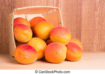 Basket of apricots on wooden table