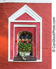 Basket of bright flowers hangs on the window
