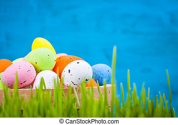 Basket of colorful Easter eggs in the grass on a blue background.