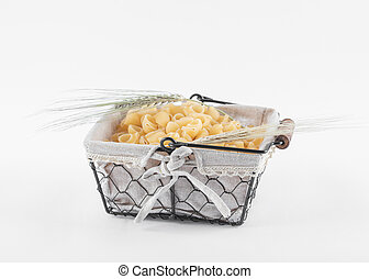 Basket of dry pasta with ears of wheat on white background
