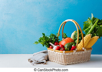 Basket of fresh vegetables on a blue background. Copy space