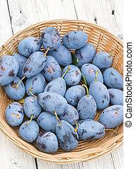 Basket of freshly picked organic plums