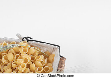 Basket of raw pasta with ears of wheat on white background