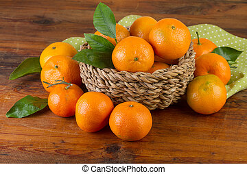 basket of tangerines with green napkin on old wooden background