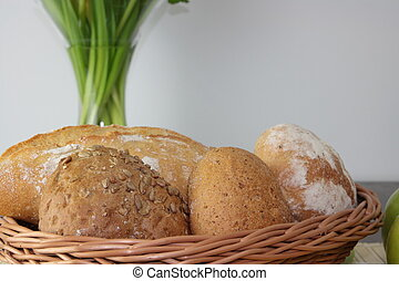 Basket of various fresh baked bread on wooden table