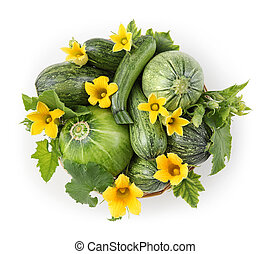 basket of zucchini, flowers and leaves isolated on white background