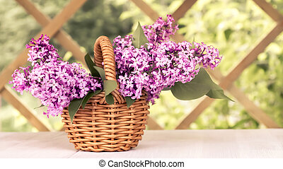 Basket with a bouquet of lilac flowers on a white wooden table in the summerhouse in the garden