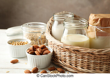 Basket with a glasses of different types milk on wooden background, space for text