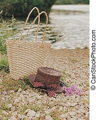 Basket with a hat on the river bank