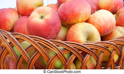 Basket with beautiful red fresh apples at the autumn fair.