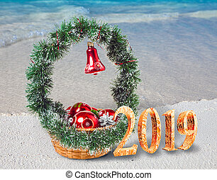 Christmas decorations on the sandy seashore and the inscription 2019- New Year's card