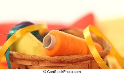 Basket with colorful threads and ribbons, close up - A small...