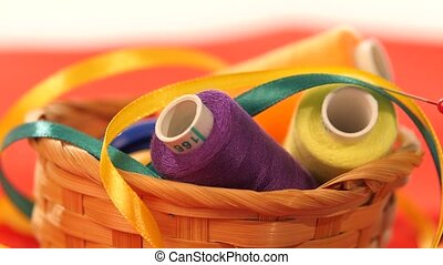 Basket with colorful threads, needles and ribbons, close up...