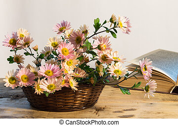 basket with delicate bouquet of chrysanthemums on a background of an open book