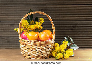 Basket with easter eggs and flowers on a wooden background.