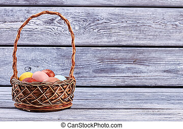 Basket with eggs on wood.