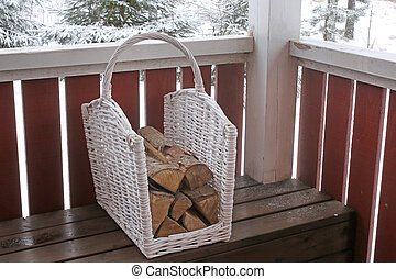 Basket with firewood on a wooden verandah