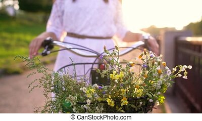 Basket with flowers close-up. Woman standing near her bicycle at sunset.