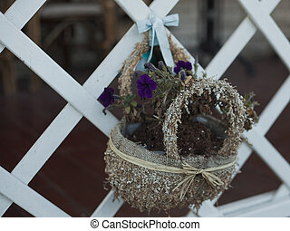 Basket with flowers on a white fence