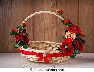 Basket with flowers to celebrate Easter on a wooden background