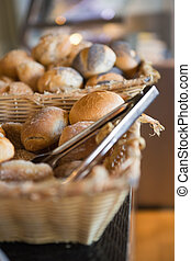 Basket with fresh bread and tongs at the bakery