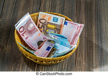 basket with money from donations - a basket with money for...