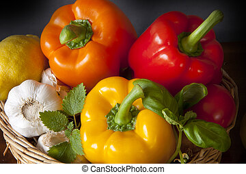 Basket with peppers, garlic, lemon and herbs