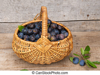 basket with plums on a wood background