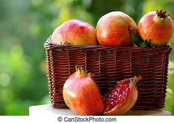 basket with red fruits of the Autumn:Pomegranates