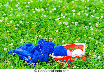 basket with skeins of wool and knitting on the green grass