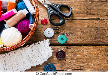 basket with thread and yarn on a wooden background