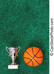 Basketball ball, a cup against green artificial turf