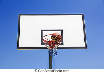 Basketball ball hit the basket in the blue sky background