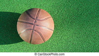 Basketball ball on green field floor