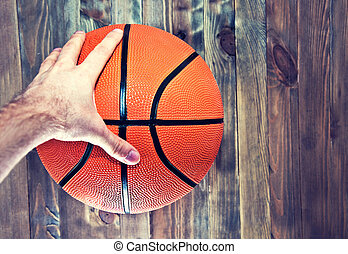 Basketball ball on wooden hardwood floor grabbing by hand.