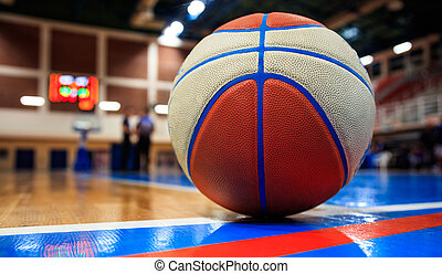 Basketball ball placed on court floor. Blurred arena with defocused people.