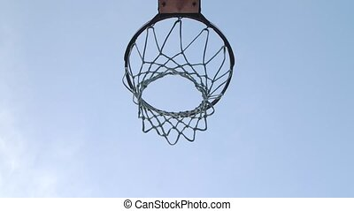 Basketball balls falls through the hoop towards the camera and hits the ring. Bottom view. Close up. Slow motion.