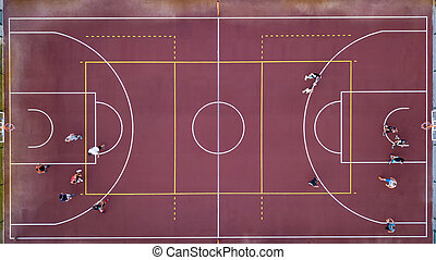Basketball court with players and ball. Sports game in basketball. View strictly from above with the drone.