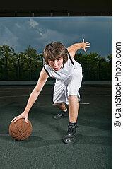 Basketball dribbling - Teenage boy with basketball at the...
