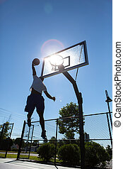 Basketball Dunker Silhouette - A young basketball player...
