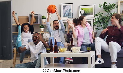 Basketball fans watching sports game on TV at home...