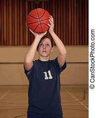 A young woman shoots a basketball in a gym.