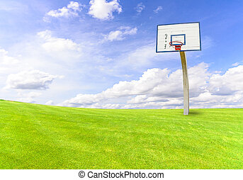 basketball goal on green field with blue sky