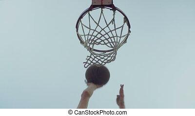 Basketball going through outdoor basketball hoop over blue...