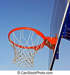 Basketball hoop against a blue sky.