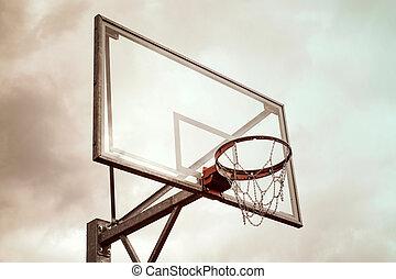 Basketball hoop against a rainy sky