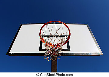 Basketball hoop against blue sky in a playground seen from under the rim (hoop)
