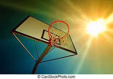 Basketball hoop against the warm summer sky.