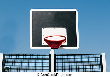 Basketball hoop outside with blue sky background