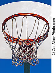 Basketball hoop with netting against blue sky